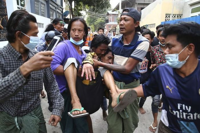 Seorang pria digotong setelah terkena tembakan polisi di Mandalay, Myanmar, pada Sabtu (20/2/2021). Polisi mulai menggunakan peluru karet dan peluru tajam untuk membubarkan massa anti-kudeta