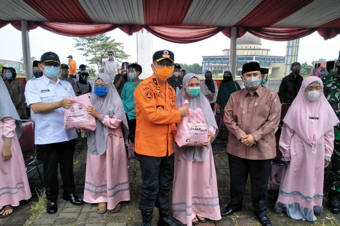 Kepala Badan Penanggulangan Bencana Daerah (BPBD) Jawa Barat Dani Ramdan (kemeja oranye) secara simbolis memberikan paket bantuan di Gema Ramadhan Jabar Juara, Rabu (5/4/2021)