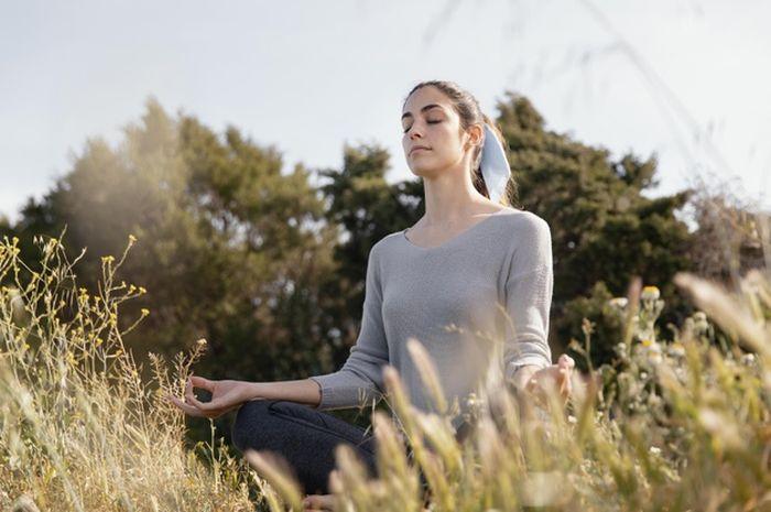 Ilustrasi seorang perempuan sedang yoga.