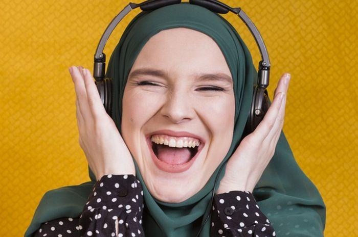 Ilustrasi seorang muslimah mendengarkan musik.