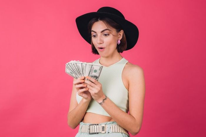 Seorang wanita yang tengah memegang uang.